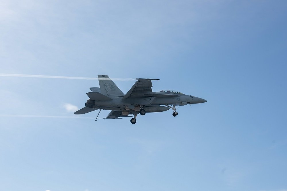 An F/A-18F Super Hornet, with Strike Fighter Squadron (VFA) 41, flies over USS John C. Stennis (CVN 74).